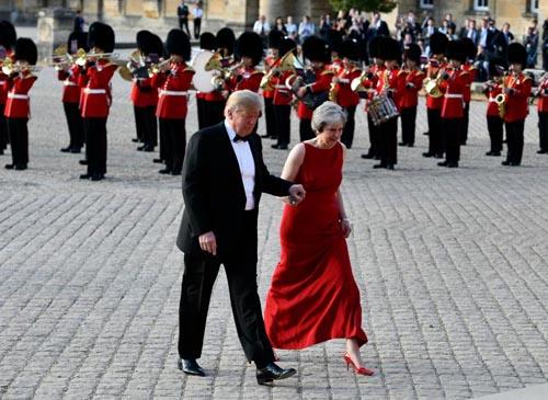 Trump cầm tay bà May khi họ tới dự bữa tối ở Cung điện Blenheim hôm 12/7. Ảnh: AP.