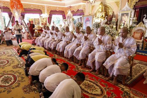 Các em quỳ xuống trước những nhà sư tụng kinh cầu nguyện và di ảnh của thợ lặn Saman Kunan. Ảnh: AFP.