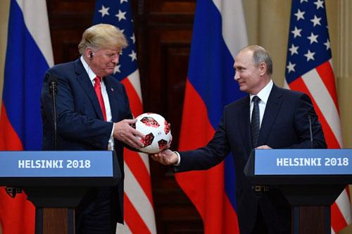 Trump (trái) nhận quả bóng từ Putin trong họp báo sau hội nghị thượng đỉnh. Ảnh: AFP.