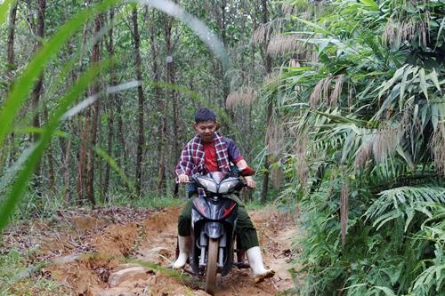 Anh Minh cùng vợ băng qua đoạn đường dốc đày sỏi đá. Ảnh: Võ Thạnh