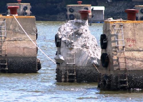 Sau khi thành phố chuyển thành dự án Cảng cá Cát Bà, một số hạng mục thuộc dự án cũ phải dỡ bỏ, điều chỉnh, trong đó trụ neo tàu đang được dỡ bỏ. Ảnh: Giang Chinh
