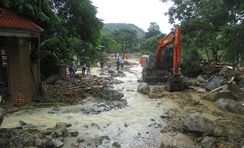 Lực lượng chức năng huy động máy xúc lật những tảng đá lớn ven suối tìm nạn nhân mất tích. Ảnh: Lê Hoàng.