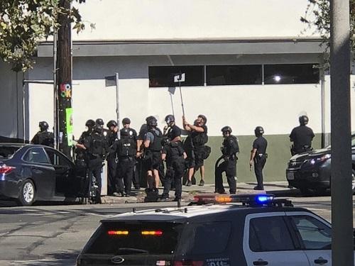 Cảnh sát Los Angeles chiếu gương quan sát tình hình trong siêu thị Trader Joe hôm 21/7. Ảnh: AFP.
