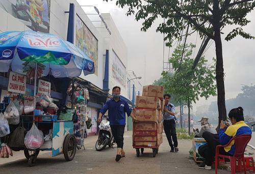 Nhân viên siêu thị kéo hàng hóa di dời. Ản: Sơn Hòa