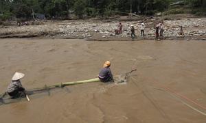 Dân vùng lũ kết bè mảng chở người qua suối