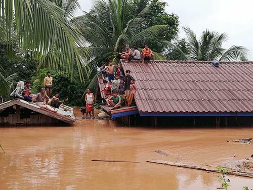 Người dân trèo lên nóc nhà tránh lũ ở huyện Sanamxay, tỉnh Attapeu, đông nam Lào
