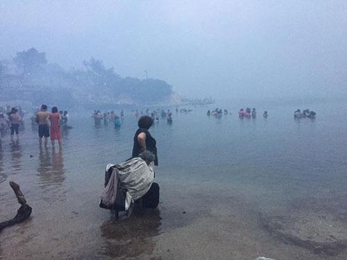 Nhiều người ở làng Mati phải xuống biển để trốn bị ngọn lửa thiêu đốt. Ảnh: Twitter.
