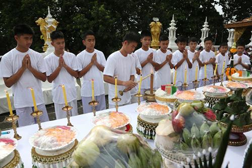 Huấn luyện viên Ekkapol Ake Chantawong thắp nến cùng 11 thành viên đội bóng tại buổi lễ ở một ngôi chùa tỉnh Chiang Rai hôm nay. Ảnh: AP