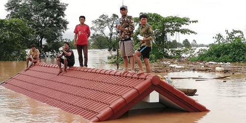 Người dân đứng trên nóc nhà chờ giải cứu khi nước lũ dâng cao do vỡ đập. Ảnh: Attapeu Today