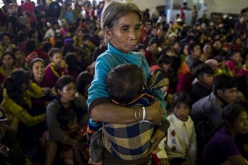 Một phụ nữ lớn tuổi bế một đứa trẻ trong khi những người cùng làng sơ tán khỏi nước lũ do sự cố vỡ đập tìm nơi trú ẩn tại thị trấn Paksong, tỉnh Champasak hôm 25/7. Ảnh: AFP.