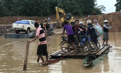 Người dân di chuyển trên một chiếc bè tự chế tại Attapeu ngày 25/7. Ảnh: AFP.
