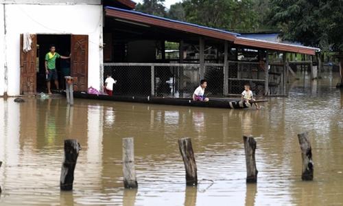 Trẻ em ngồi trên thuyền trước căn nhà bị ngập của mình tại Attapeu ngày 25/7. Ảnh: AFP.
