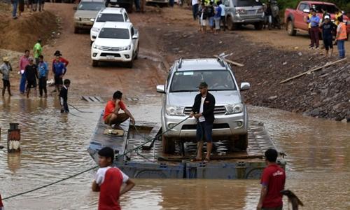 Người dân di chuyển bằng phà tự chế tại Attapeu, Lào ngày 25/7. Ảnh: AFP.