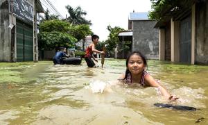 Trẻ em ngoại thành Hà Nội nô đùa trong nước lũ