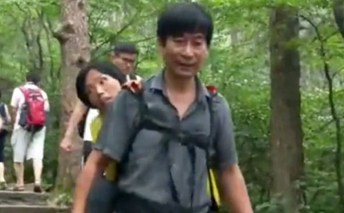 Wang Xiaomin cõng vợ lên núi bằng cách đeo đai hỗ trợ. Ảnh: Pear.