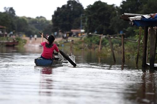 Người dân ở Sanamxai, Attapeu, Lào ngày 25/7 di chuyển bằng thuyền vì ngập lụt. Ảnh: AFP.