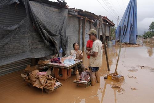 Một gia đình ngồi trên ngôi nhà ngập bùn sau khi lũ rút ở huyện Sanamxay, tỉnh Attapeu, hôm nay. Ảnh: AFP