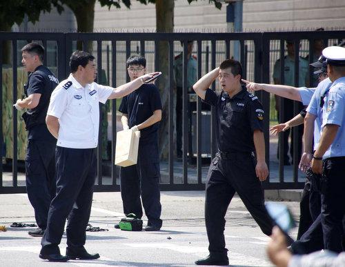 Lực lượng an ninh Trung Quốc bên ngoài đại sứ quán Mỹ sau vụ nổ. Ảnh: Reuters.