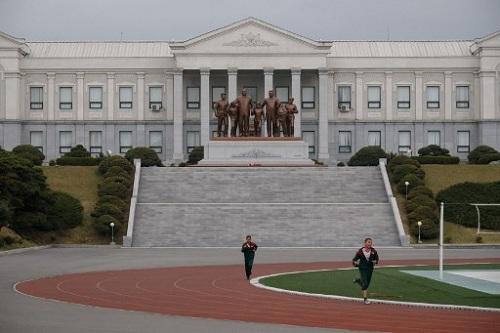 Tượng cố lãnh đạo Kim Nhật Thành và Kim Jong Il cùng các em nhỏ nhìn ra sân vận động trong trường. Ảnh: AFP.