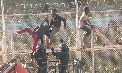 Người di cư châu Phi trèo qua hàng rào biên giới từ Morocco vào Ceuta, Tây Ban Nha hôm 26/7. Ảnh: Reuters.