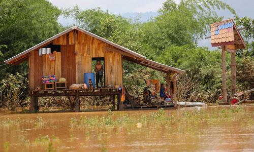 Một ngôi nhà ở bản Khokkong, huyện Sanamxai bị cô lập giữa dòng nước lũ hôm 26/7.Ảnh: Thành Nguyễn