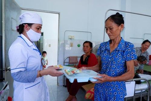 Bệnh nhân nhận suất cơm do Khoa dinh dưỡng, Bệnh viện Đặng Thùy Trâm nấu. Ảnh: Phạm Linh.