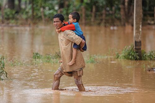 Người đàn ông Lào bế con lội qua dòng nước lũ đang rút dần ở huyện Sanamxay, tỉnh Attapeu hôm 26/7. Ảnh: Thành Nguyễn