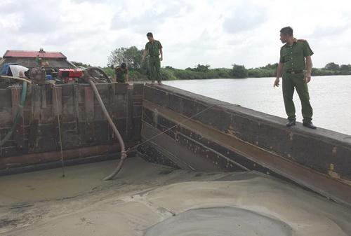 Cảnh sát khám nghiệm thuyền chứa cát của nhóm hút cát trái phép để lại. Ảnh: Thái Hà