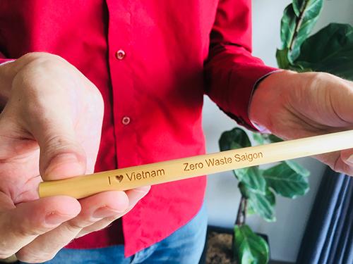 Michael Burdge giới thiệu chiếc ống hút làm bằng tre khắc dòng chữ Tôi yêu Việt Nam và Zero Waste Saigon. Ảnh: Hạnh Phạm.
