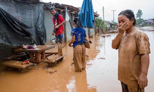 Người dân bản Kok Kong dọn dẹp ngôi nhà bị ngập bùn hôm 27/6. Ảnh: Thành Nguyễn.