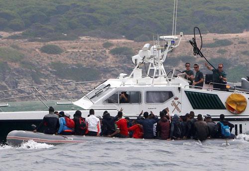 Thuyền của lực lượng tuần tra biên giới Tây Ban Nha tiếp cận xuồng chở người nhập cư gần bờ biển Del Canuelo hôm 27/7. Ảnh: Reuters.