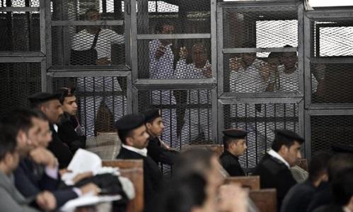 Các thành viên tổ chức Anh em Hồi giáo Ai Cập đứng trong lồng sắt trong một phiên tòa hồi tháng 5/2014. Ảnh: AFP.