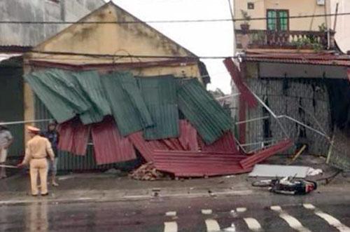 Nhiều ngôi nhà ven đường bị hư hỏng, chiếc xe máy của hai mẹ con nạn nhân cũng bị kéo lê và đâm nát phần đầu và đuôi. Ảnh: Thanh Tuân