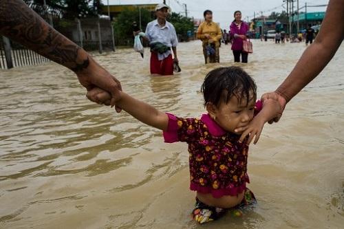 Người dân nắm tay một em bé lội qua nước lũ ở Bago, cách Yangon khoảng 68 km, hôm 29/7. Mưa lớn do ảnh hưởng của gió mùa đang trút xuống bang Karen, Mon và khu vực Bago những ngày gần đây mà không có dấu hiệu giảm bớt, làm dấy lên lo ngại rằng tình hình sẽ còn tệ hơn. Ảnh: AFP.