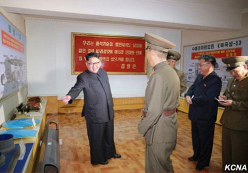 Kim Jong-un (trái) đứng cạnh mô hình tên lửa Pukkuksong-3. Ảnh: KCNA.