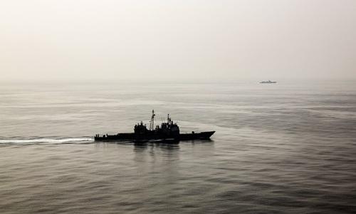 Tàu khu trục nhỏ Trung Quốc (phía xa) đeo bám tuần dương hạm Mỹ trên Biển Đông hồi tháng 3/2016. Ảnh:NYTimes