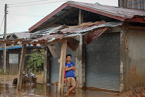 Một người dân Sanamxay trở về ngôi nhà đã hư hỏng sau khi lũ rút. Ảnh: Thành Nguyễn