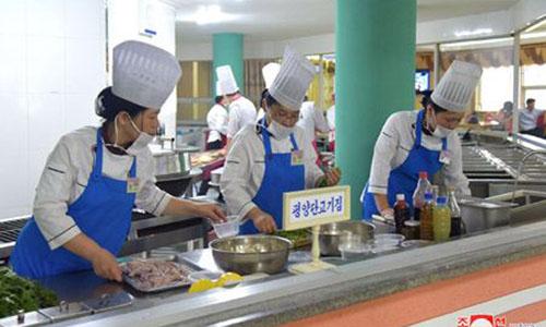 Nhân viên nhà hàng Pyongyang Dog Meat House chế biến món thịt chó trong cuộc thi diễn ra ở phố Ryomyong tuần trước. Ảnh: KCNA.