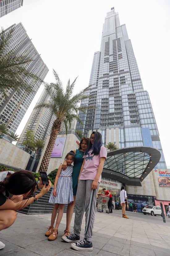 """<p class=""""Normal""""> Ở bên ngoài, nhiều người tìm mọi cách để chụp ảnh với tòa nhà cao nhất Việt Nam.</p>"""