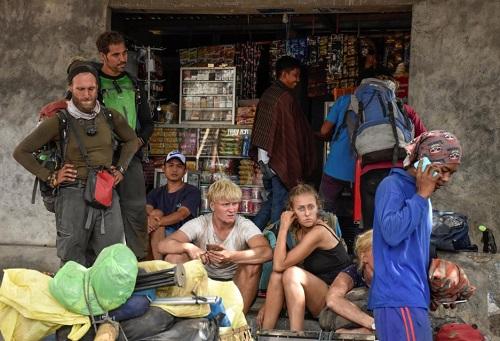 Người nước ngoài leo núi đi bộ xuống làng Sembalun ở Lombok hôm 29/7. Ảnh: Reuters.
