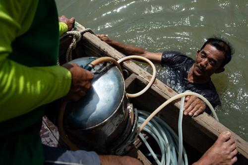 Mặc quần soóc, áo phông, Bhoomin lặn xuống lòng sông đầy rác chảy qua thủ đô Thái Lan. Ảnh: AFP.