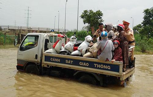 3 xe ô tô chuyên dụng của CSGT Hà Nội được huy động hàng chục lượt đưa người dân băng qua vùng ngập.