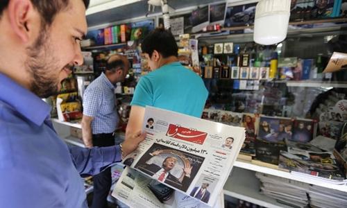 Một người ở Tehran xem tờ báo có hình Trump trên trang bìa ngày 31/7. Ảnh: AFP.