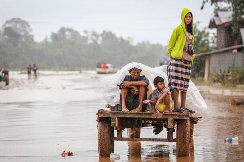 Những người sống sót trong vụ vỡ đập thủy điện ở Lào trở về nhà trên con đường ngập nước và bùn. Ảnh: Thành Nguyễn.