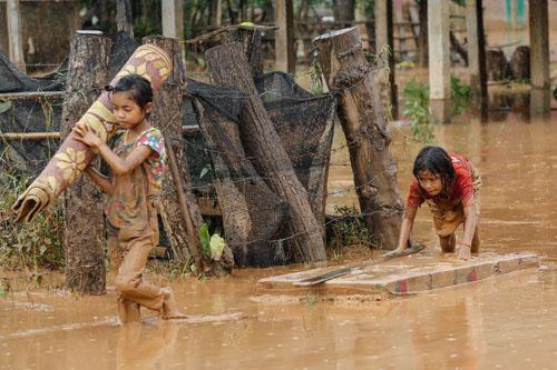 Trẻ em giúp cha mẹ dọn dẹp những gì còn sót lại trong ngôi nhà sau trận lũ kinh hoàng. Ảnh: Thành Nguyễn.