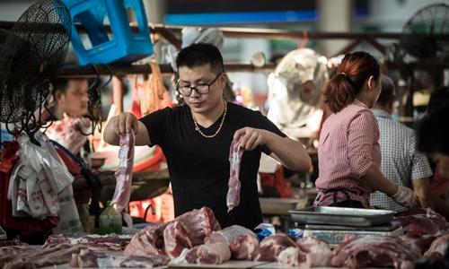 Một người bán thịt lợn tại chợ ở Chu Gia Giác. Ảnh: Washington Post.