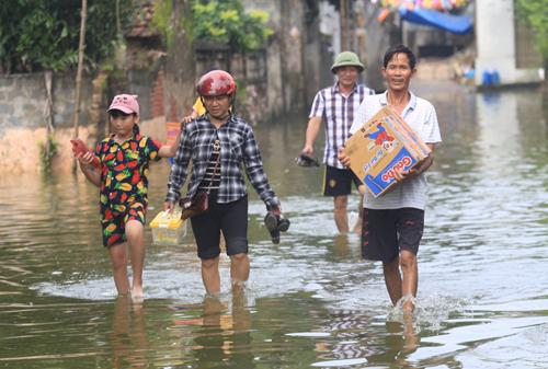 Người dân xã Nam Phương Tiến đi nhận mì tôm cứu trợ của chính quyền. Ảnh: Gia Chính.