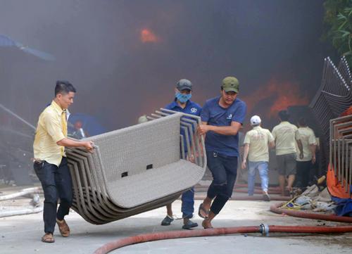 Công nhân di dời đồ khỏi đám cháy. Ảnh: Sơn Hòa