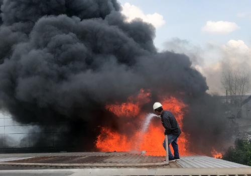 Công nhân cố dập lửa trong đám cháy. Ảnh: Tin Tin