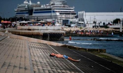 Người dân tắm nắng ở bến cảngRibeira das Naus tại Lisbon hôm 3/8. Ảnh: AFP.